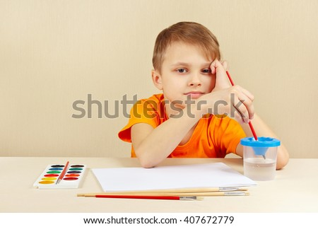 Little artist in an orange shirt going to paint colors - stock photo