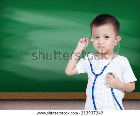 Little asia boy holding stethoscope with green chalk board - stock photo