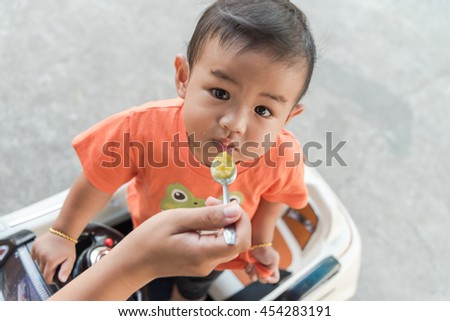 Little Asian baby boy eating rice porridge