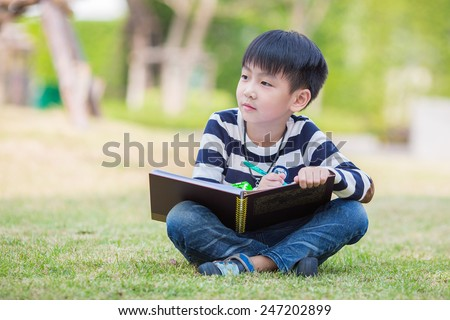 little asian boy drawing in the garden - stock photo