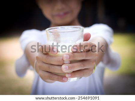 Little asian boy drinking a glass of milk - stock photo