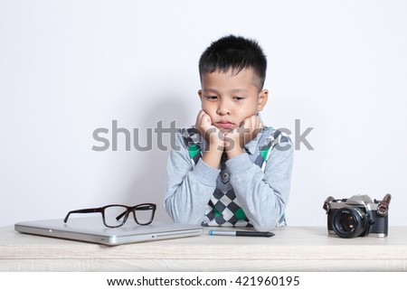 Little asian boy feeling sad and crying with laptop and camera film