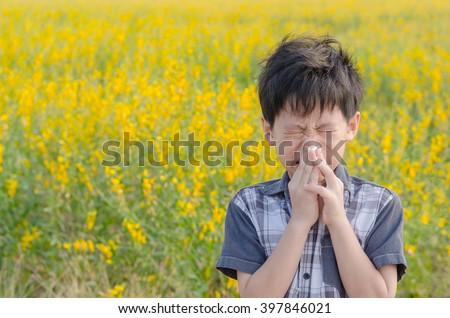 Little Asian boy has allergies from flower pollen - stock photo