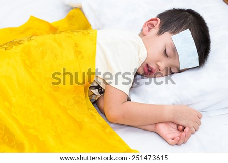 Little asian boy has fever and sleep on bed with gels fever on head - stock photo