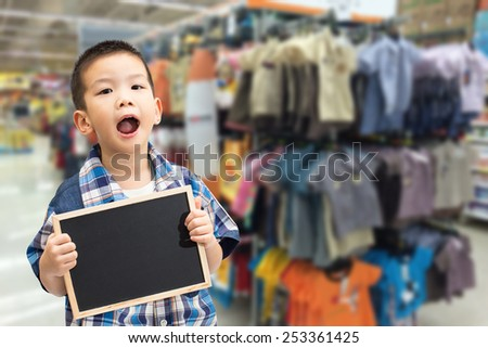 Little asian boy holding a blank blackboard with kids shirt shop background - stock photo