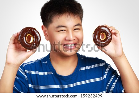 Little asian boy holding a chocolate donuts, Isolated on white background - stock photo