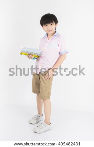 Little asian boy is holding a book. - stock photo
