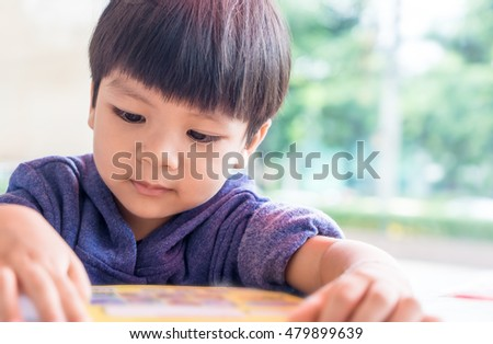 little Asian boy is reading a picture book