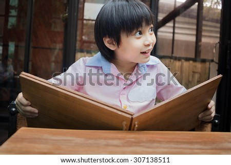 little asian boy looking at a menu in cafe, vintage filter - stock photo