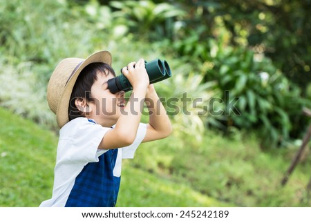 Little asian boy looking trough a binoculars with smiling face in park - stock photo