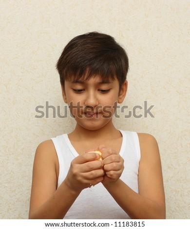 little asian boy, peeling the orange - stock photo