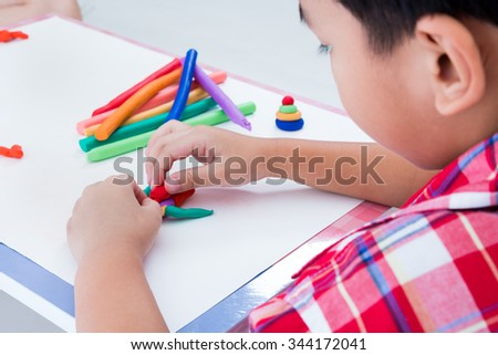 Little asian boy playing and creating toys from play dough. Child moulding robot modeling clay. Strengthen the imagination of child - stock photo