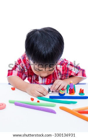Little asian boy playing and creating toys from play dough. Child moulding whale modeling clay, on white background. Strengthen the imagination of child