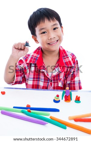 Little asian boy playing and creating toys from play dough. Child smiling and show his works from clay, over white background. Strengthen the imagination of child. - stock photo