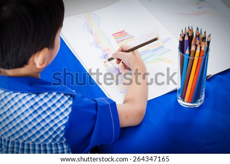 Little asian boy sitting at the table and drawing by color pencil, shot in studio - stock photo