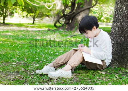 Little asian boy sitting under the tree and drawing in book - stock photo