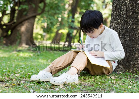 Little asian boy sitting under the tree and drawing in notebook at park - stock photo