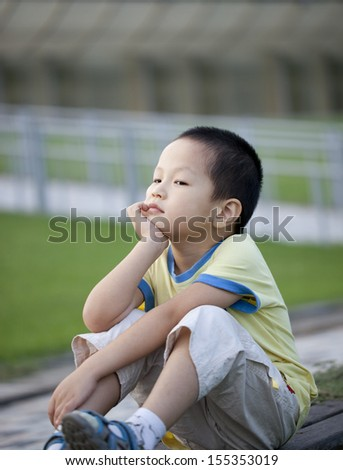 little asian boy thinking in the park