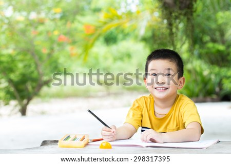 Little asian boy use pencil writing on notebook for writing book with smiling face on wooden table in the park - stock photo