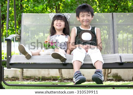 little asian brother and sister play swing in park