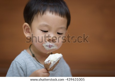 Little asian child enjoy eating an ice cream bar at home
