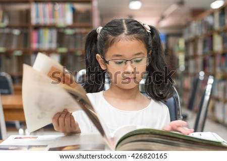 Little asian child girl w/ eyeglasses reading book school background: Lovely cute young student kid opening flipping book in archive resource collection room: National library lover month week - stock photo