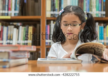Little asian child girl w/ eyeglasses studious reading book school background: Lovely cute young student kid opening flipping book in archive resource collection room National library lover month week - stock photo