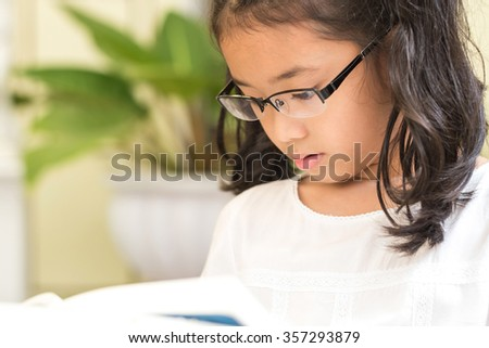 Little asian child girl wearing eyeglasses enjoy reading book w/ enjoyment, diligence (Selective focus): Lovely cute young female diligent student kid studying in with concentration in study room