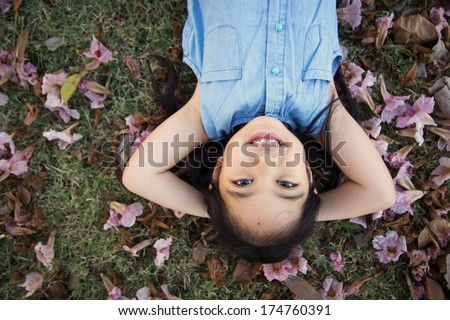 Little Asian child laying down on the flower - stock photo