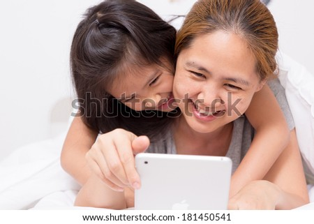 Little Asian child using tablet with mother - stock photo
