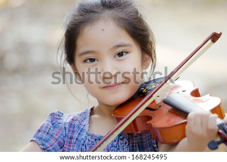 Little Asian child with violin outdoor - stock photo