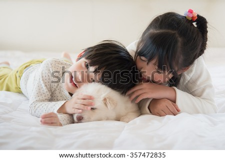 Little asian children and puppy having fun lying in bed - stock photo