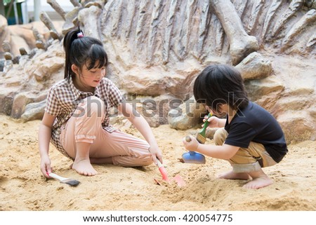 Little asian children has fun digging in the sand at adventure park