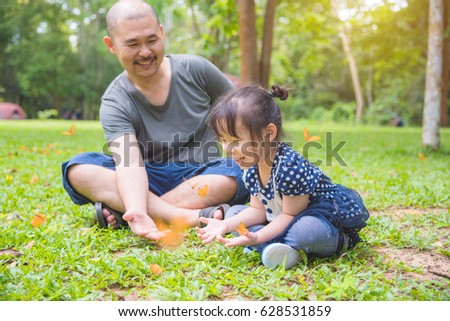 Little asian girl and her father looking at butterflies in park