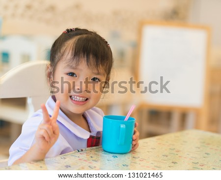 little Asian girl at restaurant - stock photo