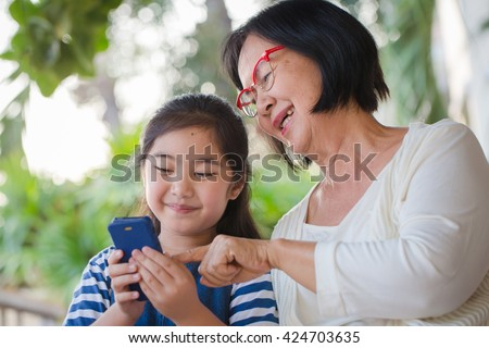 Little Asian girl calling mobile phone with her grandmother - stock photo