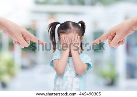 Little asian girl crying while parents scold her
