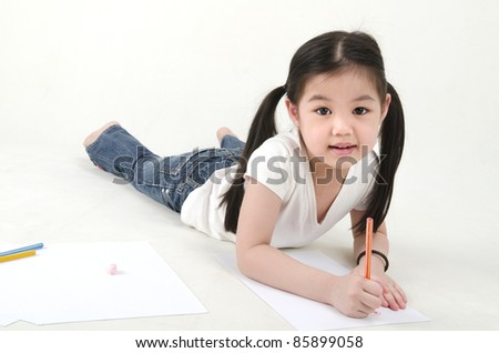 Little Asian girl drawing, lying on floo