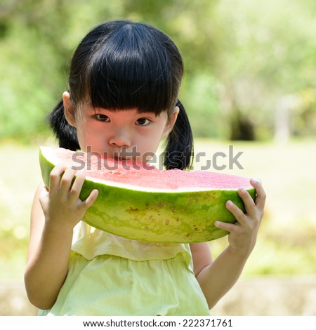 Little Asian girl eating watermelon in park - stock photo