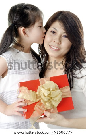 Little Asian girl giving gift for mother and kissing on mother's cheek - stock photo