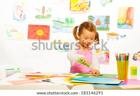 Little Asian girl gluing and making crafts with color cardboard paper - stock photo