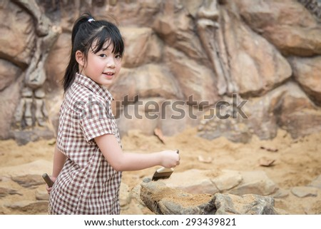 Little asian girl have fun digging in the sand at adventure park