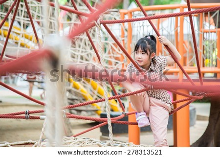 Little asian girl is having fun in adventure park - stock photo