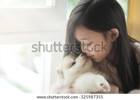 Little asian girl kissing a siberian husky puppy at the window,vintage filter - stock photo