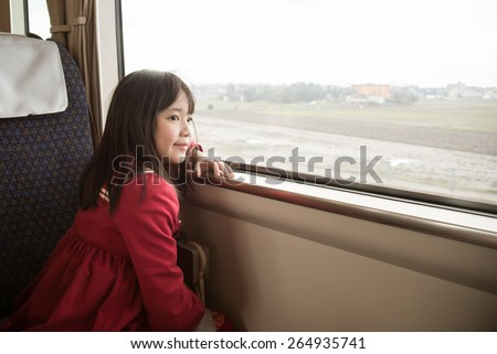 Little asian girl looking through window. She travels on a train,vintage filter - stock photo