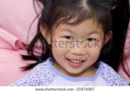 Little Asian girl lying on bed - stock photo