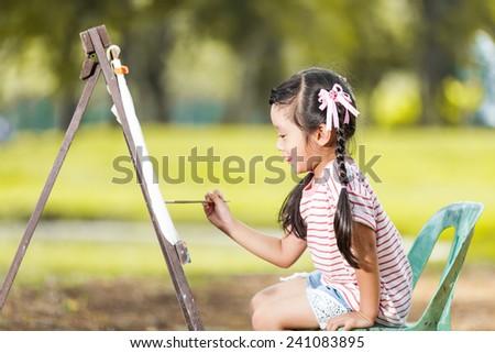 Little Asian girl painting on easel - stock photo