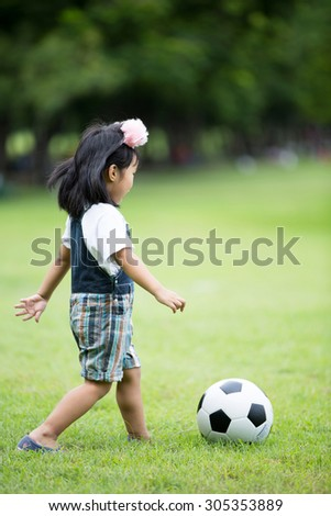 Little asian girl playing football at the park,Bangkok Thailand - stock photo