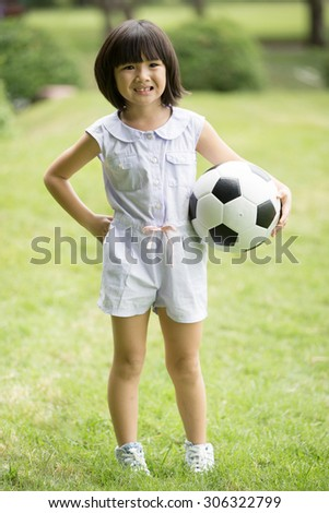 Little asian girl playing football at the park,Bangkok Thailand