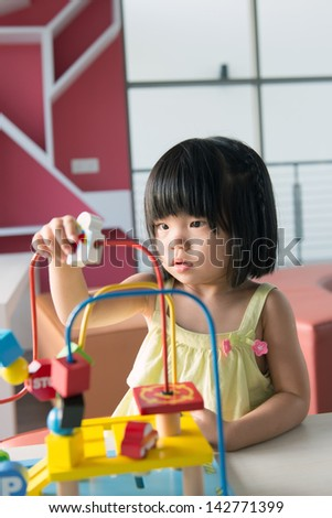 Little Asian girl playing with toy portrait - stock photo